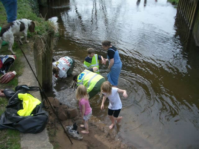 Photo of volunteers fishing a trolley out of the river
